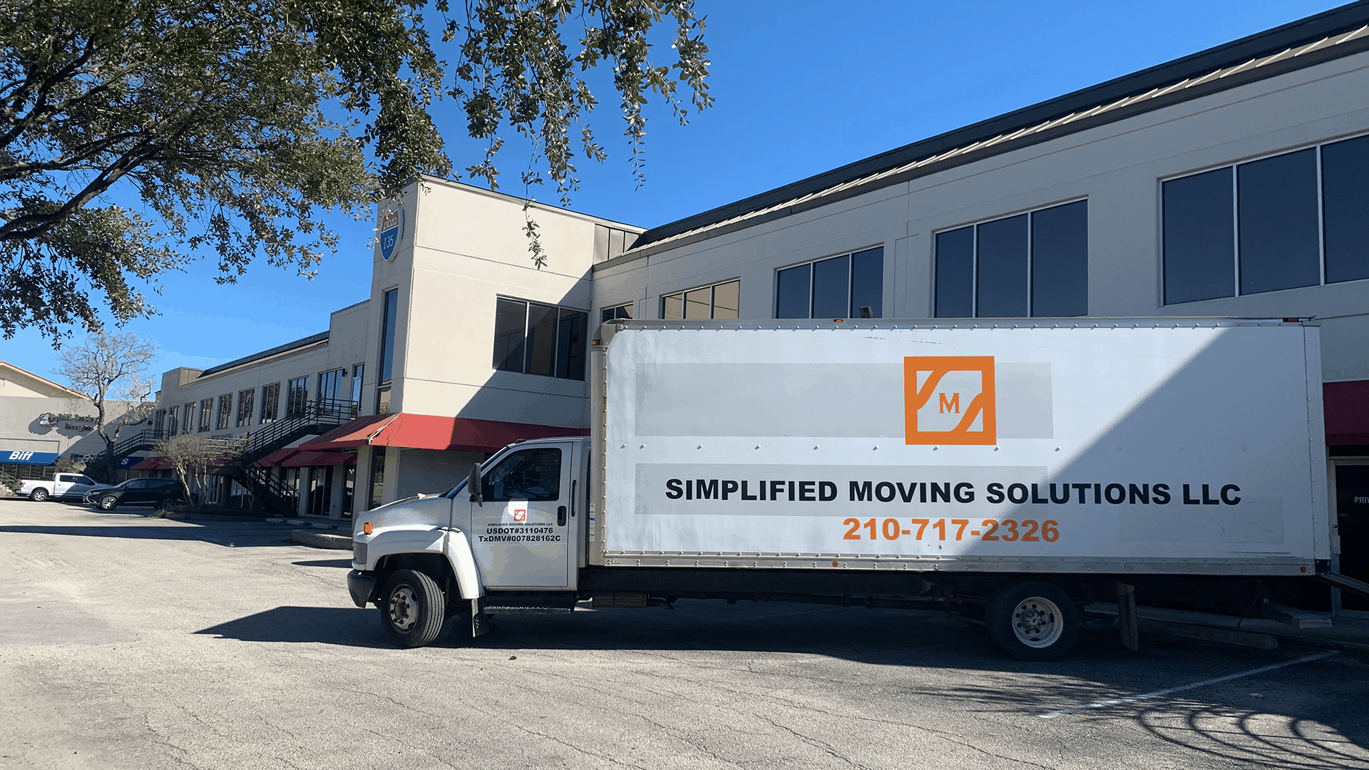 Image of large moving truck parked at commercial business